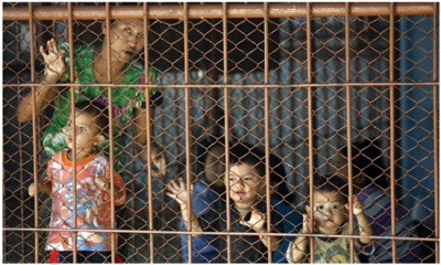 Burmese children stand behind bars with other detainees in a crowded detention cell in Mae Sot, Thailand